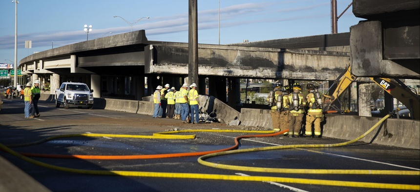 Construction workers and firefighters survey a section of an overpass that collapsed from a large fire on Interstate 85 in Atlanta, Friday, March 31, 2017.