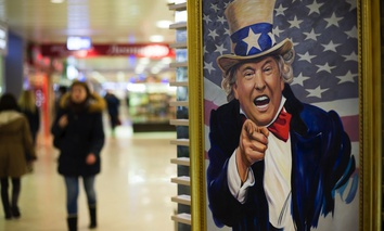 People walk past a caricature picture of U.S. President Donald Trump on sale in a shopping mall in Moscow, Russia.
