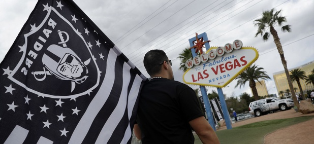 Matt Gutierrez carries a raiders flag by a sign welcoming visitors to Las Vegas.