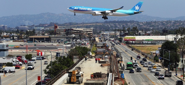 An airliner prepares to land at Los Angeles International Airport over the Metro Crenshaw/LAX Line, en extension of the city's transportation network as the city seeks the 2024 Summer Olympic Games.