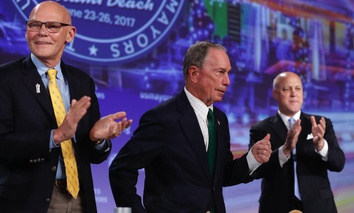 Michael Bloomberg, center, gestures as James Carville, left, and New Orleans Mayor Mitch Landrieu, right, applaud after his speech at the annual U.S. Conference of Mayors meeting Monday in Miami Beach, Fla.