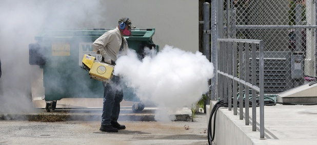 A Miami-Dade County mosquito control worker sprays around a school in the Wynwood area of Miami on Monday, Aug. 1, 2016.