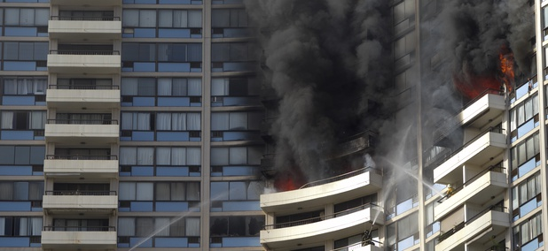 Firefighters on several balconies spray water upwards while trying to contain a fire at the Marco Polo apartment complex.