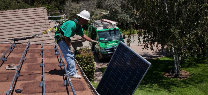 A worker installs solar panels on a home in Oak View, California.