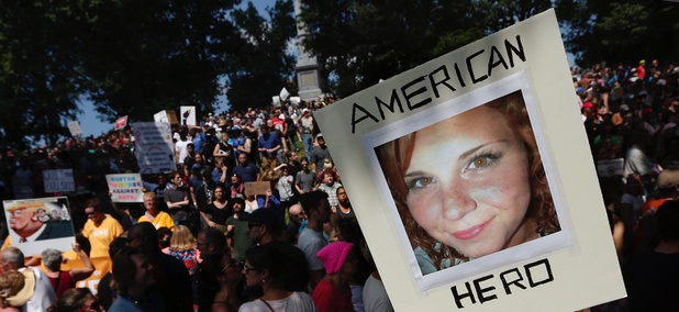 "A counter-protester holds a photo of Heather Heyer on Boston Common at a ""Free Speech"" rally organized by conservative activists Saturday in Boston."
