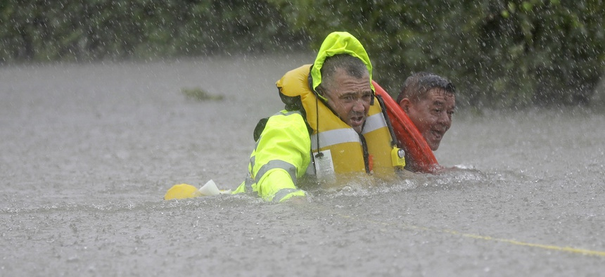 Wilford Martinez, right, is rescued from his flooded car along Interstate 610 in floodwaters from Tropical Storm Harvey on Sunday, Aug. 27, 2017, in Houston, Texas.