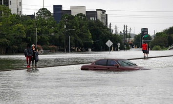 Evacuees walk along a median of Interstate 610 covered in floodwaters from Tropical Storm Harvey Sunday, Aug. 27, 2017, in Houston.