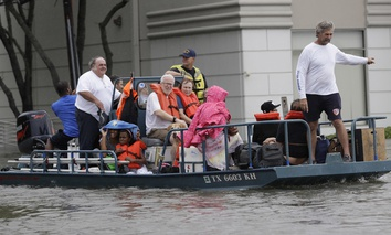 Residents are evacuated from their homes surrounded by floodwaters from Tropical Storm Harvey Sunday, Aug. 27, 2017, in Houston.