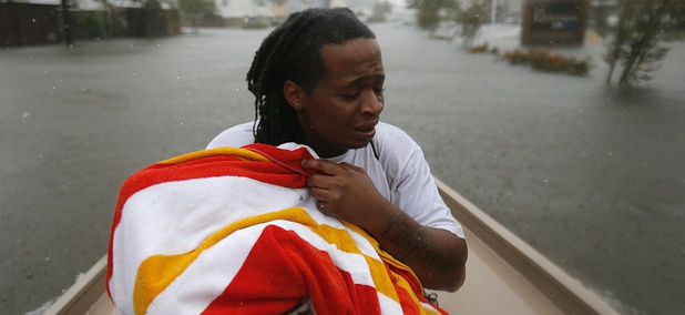 Demetres Fair holds a towel over his daughter Damouri Fair, 2, as they are rescued by boat by members of the Louisiana Department of Wildlife and Fisheries and the Houston Fire Department on Monday in Houston.