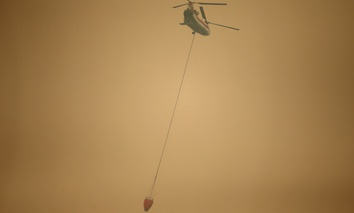 A helicopter with a water bucket flies through dense smoke near Stevenson, Wash., Wednesday, Sept. 6, 2017, as it works to battle the Eagle Creek wildfire on the Oregon side of the Columbia River Gorge.