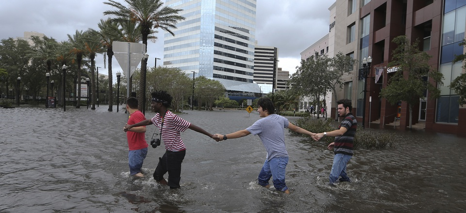 Four people link arms as they explore the flooded Jacksonville Landing in the wake Hurricane Irma on Monday, Sept. 11, 2017, in Jacksonville, Fla.