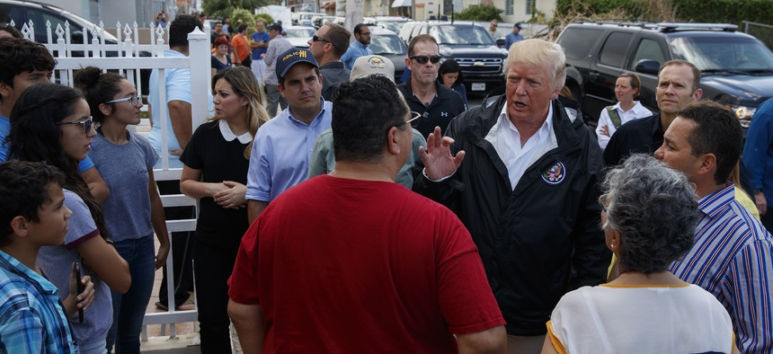 President Donald Trump talks with residents during a tour a neighborhood impacted by Hurricane Maria, Tuesday, Oct. 3, 2017, in Guaynabo, Puerto Rico.