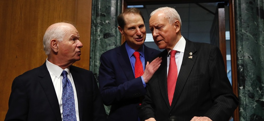 Sen. Ben Cardin, left, talks with Ranking Member Sen. Ron Wyden, and Senate Finance Committee Chairman Orrin Hatch.