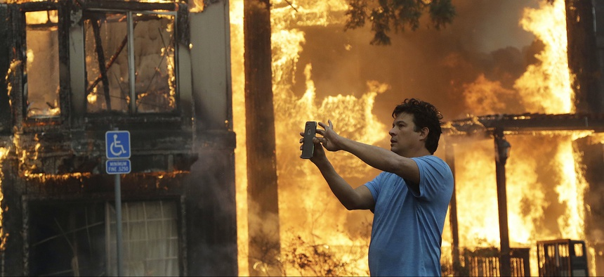 Rudy Habibe, from Puerto Rico, stands by the burning Hilton Sonoma Wine Country hotel, where he was a guest, in Santa Rosa, Calif., Monday, Oct. 9, 2017.