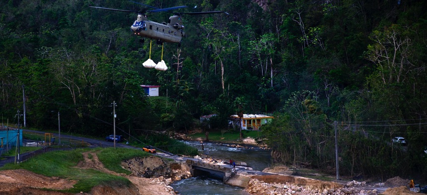 A U.S. Army helicopter transports material to repair the Guajataca Dam, damaged during Hurricane Maria, in Quebradillas, Puerto Rico on Tuesday.
