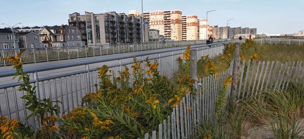 Five years after Superstorm Sandy, dune plantings border a broad concrete boardwalk separating residential buildings, left, from the beach in Rockaway Beach in the Queens borough of New York City.