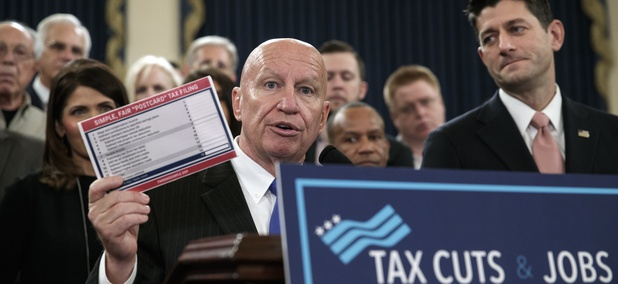 """House Ways and Means Committee Chairman Kevin Brady, R-Texas, joined by Speaker of the House Paul Ryan, R-Wis., right, holds a proposed """"postcard tax filing form"""" as they unveil the GOP's far-reaching tax overhaul, on Thursday, Nov. 2, 2017."""