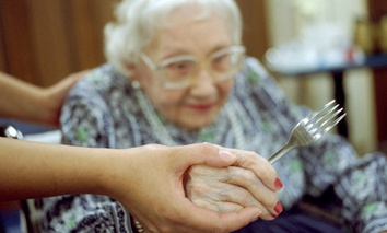An elderly woman is assisted with eating at a nursing home in the Bronx, New York.