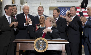 President Donald Trump hands a pen to Sen Orrin Hatch, R-Utah, after signing a proclamation to shrink the size of Bears Ears and Grand Staircase Escalante national monuments, Monday, Dec. 4, 2017, in Salt Lake City.