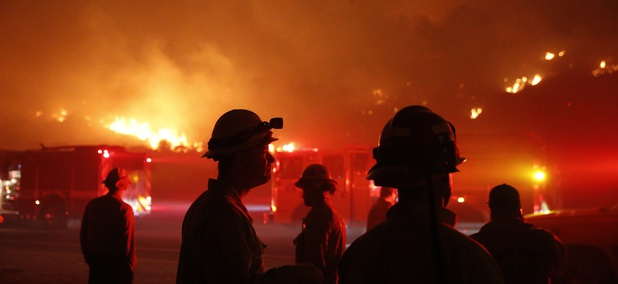 Firefighters gather in front of a residential area as a wildfire burns along the 101 Freeway Tuesday, Dec. 5, 2017, in Ventura, Calif.
