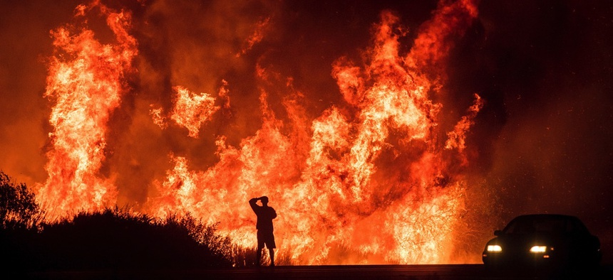 A motorists on Highway 101 watches flames from the Thomas fire leap above the roadway north of Ventura, Calif., on Wednesday, Dec. 6, 2017.