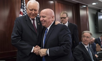 House Ways and Means Committee Chairman Kevin Brady, R-Texas, center, embraces Senate Finance Committee Chairman Orrin Hatch, R-Utah, left, on Capitol Hill in Washington, Wednesday, Dec. 13, 2017.