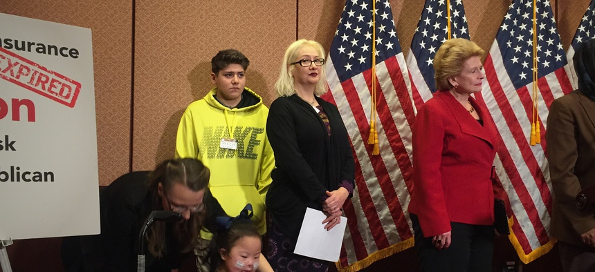 Connie Cavara (center) stands alongside her son, Diego, 13 as she waits to speak on behalf of the Children's Health Insurance Program.