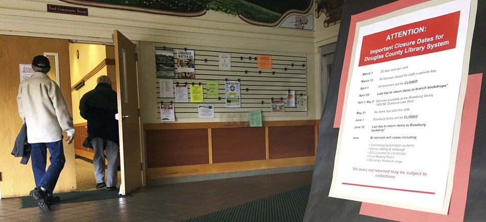 In this April 7, 2107 photo, residents in Douglas County, Ore., walk into a community meeting at the main branch of the Douglas County library system in Roseburg, as a sign in the foreground lists important closure dates.