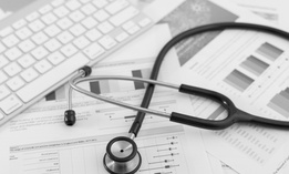 Stethoscope with financial statement on the desk.