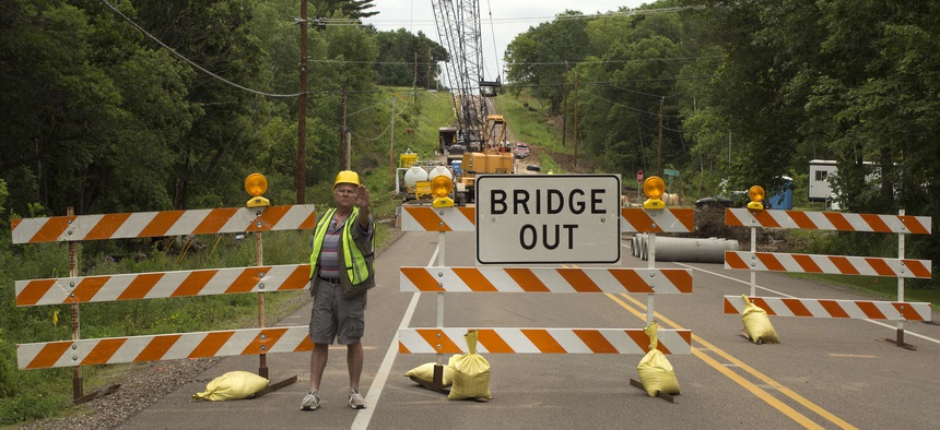 A highway worker directs traffic around a bridge under construction in River Falls, Wisconsin, during August 2016.