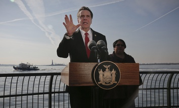New York Gov. Andrew Cuomo holds a press conference with the Statue of Liberty in the distance behind him, Sunday Jan. 21, 2018, in New York.