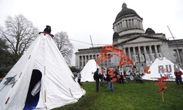 Activists gather around structures erected on a grassy area in front of the Washington State legislature in Olympia.