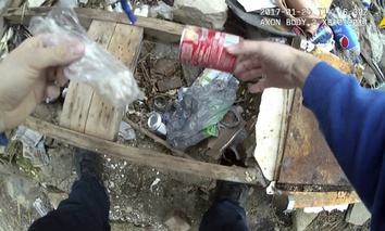 This frame grab pulled from body camera footage that was filmed Jan. 24, 2017, and released by the Maryland Office of the Public Defender shows Baltimore Police Officer Richard Pinheiro removing a baggie of drugs from a soup can in Baltimore.