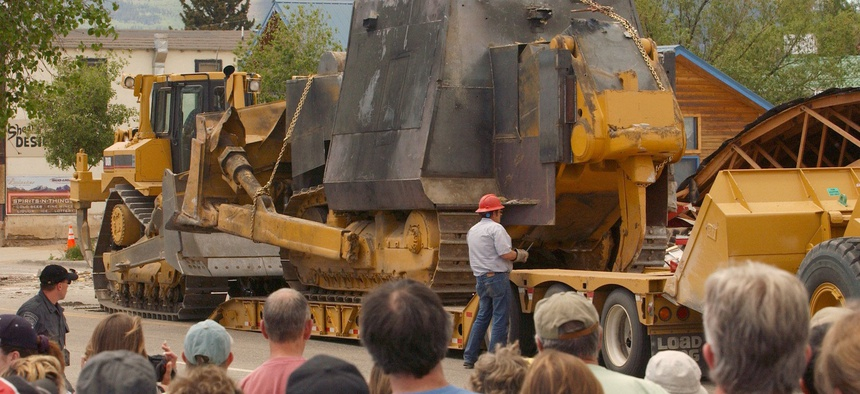 A crowd of onlookers watches as a makeshift armored bulldozer is loaded onto a tractor-trailer after being extracated from the rubble of a warehouse in Granby, Colo., Saturday afternoon, June 5, 2004.