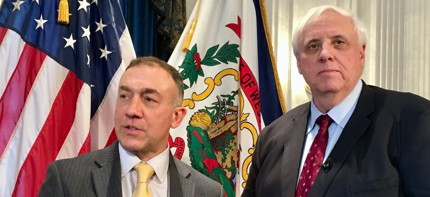Dr. Michael Brumage, left, is joined by West Virginia Gov. Jim Justice, right, at a news conference Monday, Feb. 5, 2018, at the Capitol in Charleston, West Virginia.