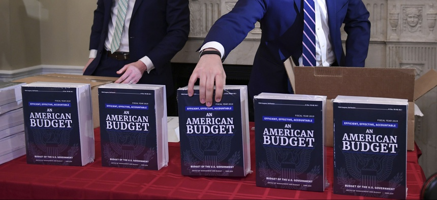 James Knable, left, and Jeffrey Freeland, right, help to unpack copies of the President's FY19 Budget after it arrived at the House Budget Committee office on Capitol Hill in Washington, Monday, Feb. 12, 2018.