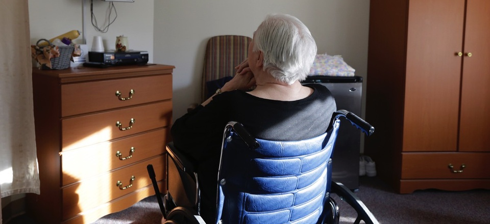 An elderly woman who has suffered abuse by a relative sits in her room in a retirement community in Mason, Ohio.