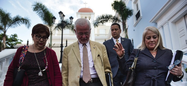 Puerto Rico Justice Secretary Wanda Vazquez-Garced, far right, walks with colleagues to a press conference in San Juan on Jan. 16 addressing the island's homicide surge.