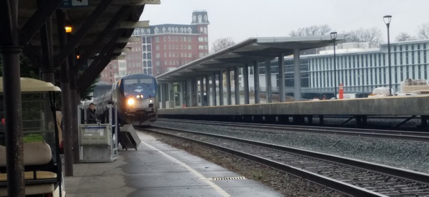 An Amtrak train pulls into the current train station, at left, which sits adjacent to the new Raleigh Union Station complex, at right.