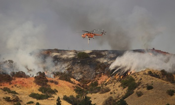 An Erickson Air-Crane helicopter flies between flames of the La Tuna Fire in Los Angeles in September 2017.
