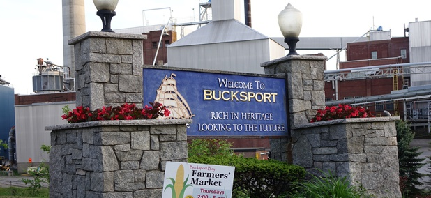 A welcome sign in Bucksport, Maine stands in front of the former Verso paper mill, now demolished.