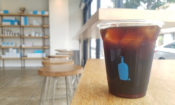 A cup of cold brew coffee and interior view of a Blue Bottle Coffee Co. location in Los Angeles.