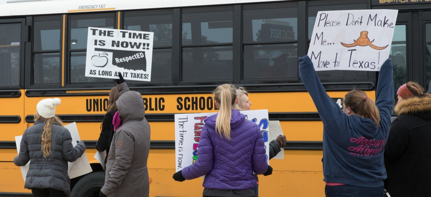 A school bus passes a group of striking teachers in Tulsa, Oklahoma on April 2.