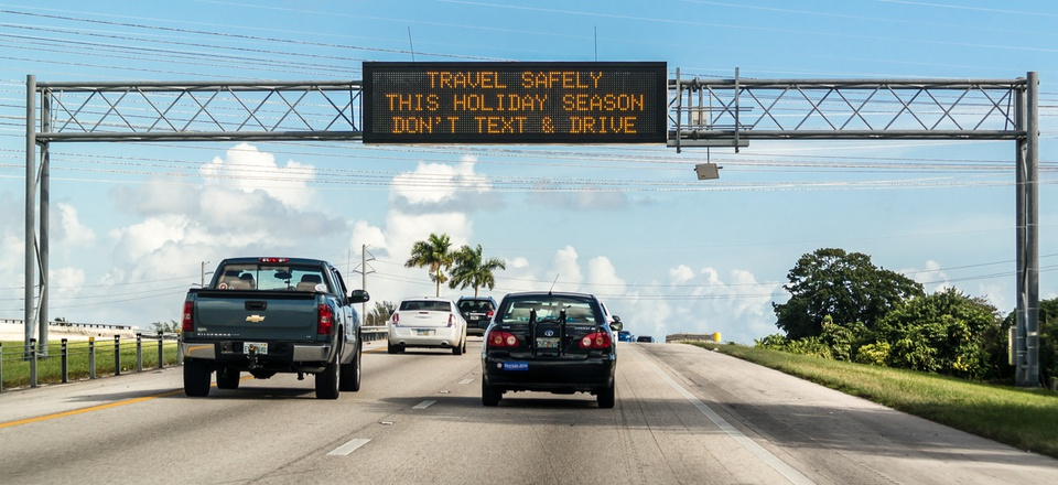 Electronic variable message board on matrix billboard on highway warning drivers not to text and drive.