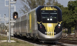 A Brightline train approaches a railroad crossing, Thursday, Jan. 18, 2018, in Fort Lauderdale, Fla.