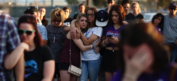 People comfort each other during a vigil for victims and survivors of a mass shooting in Las Vegas six months after the October violence.