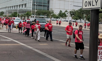 Arizona teachers dressed up in red shirts marching back from first day of their recent walkout.