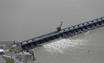 Workers open the gates of the Bonnet Carre spillway, a river diversion structure, which diverts water from the rising Mississippi River, left, to Lake Pontchartrain, in Norco, La., Thursday, March 8, 2018.