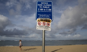 This August 2015 photo shows a warning sign posted on Waikiki Beach in Honolulu after sewage from a treatment plant spilled near the ocean.