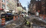 Utility workers dig in a street as they replace an aging water main, Tuesday, April 5, 2016, in New York.